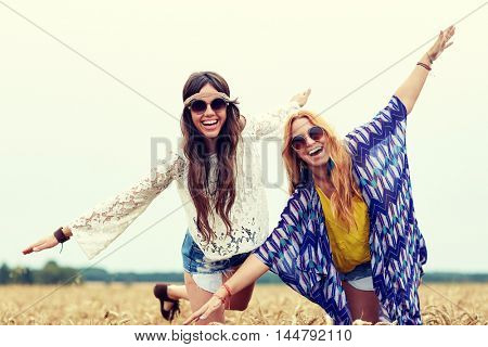nature, summer, youth culture, friendship and people concept - smiling young hippie women having fun on cereal field