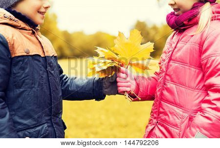 childhood, leisure, friendship and people concept - happy little boy giving maple leaves to girl in autumn park