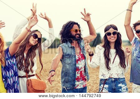 nature, summer, youth culture and people concept - happy young hippie friends dancing on cereal field
