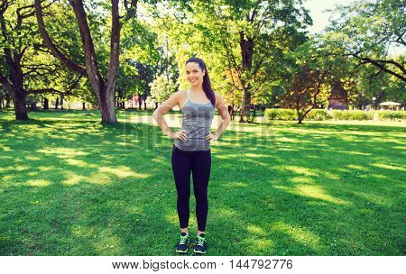 fitness, sport, people and healthy lifestyle concept - happy young woman exercising outdoors