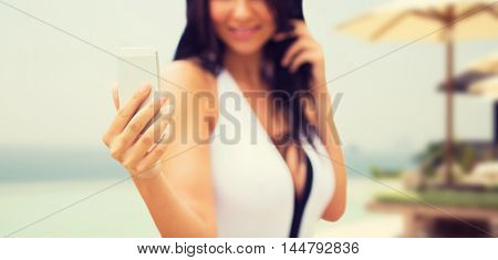 summer, travel, tourism, technology and people concept - close up of sexy young woman taking selfie with smartphone over resort beach with parasols and swimming pool background