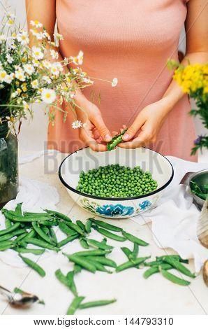 Woman Podding Fresh Peas In The Kitchen. Woman Podding Fresh Pea