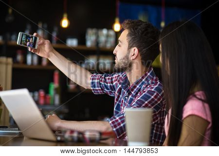 Portrait of romantic couple having date in restaurant or cafe. People posing for camera of mobile or smart phone while sitting in front of laptop computer.