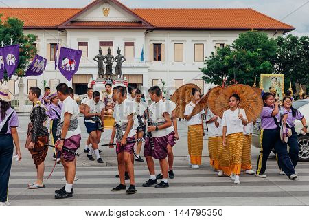 CHIANG MAI THAILAND - AUGUST 24: Young boys and girls in festival costumes parade near the Three Kings Monument on August 24 2016 in Chiang Mai Thailand.