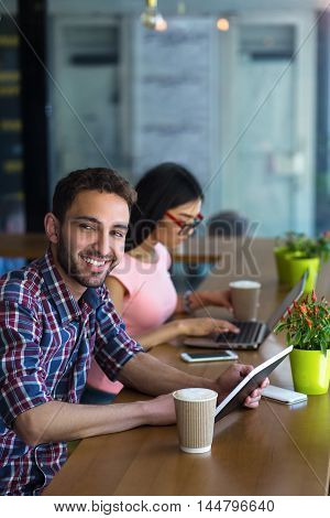 Business or freelance man and woman working in restaurant. Happy handsome man holding tablet PC and looking at camera.