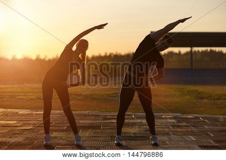 Fitness workout outdoors: young adults doing warming up exercises outdoors at sunset.