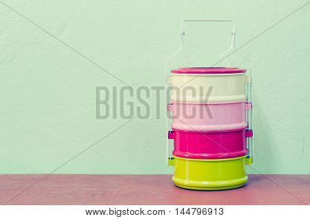 metal Tiffin thai food carrier on mint background in pastel color