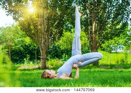 Beautiful young woman doing yoga in the summer park. Healthy lifestyle. Various yoga postures.