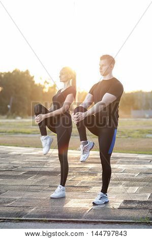 Young healthy couple warming up before exercising or jogging in park. Workout outdoors.