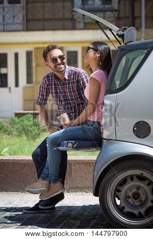 Picture of happy tourist man and woman communicating, smiling while sitting in car. People in sunglasses posing outdoors.