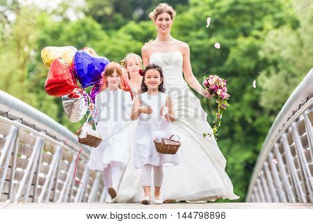 Wedding bride with flower children or bridesmaid in white dress and flower baskets