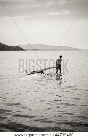 Young man dragging his windsurf board and sail on sea surface
