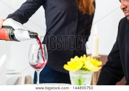 Waitress pouring wine in glass at fine restaurant