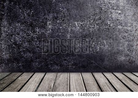 Old wooden table in front of black chalkboard vintage wall. Blackboard with wooden floor for your text. View with copyspace