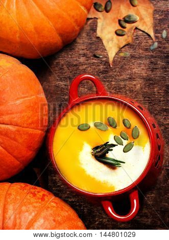 Pumpkin soup with cream on dark wooden background Top view image