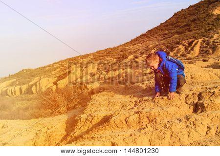 little boy climbing in mountains, active family concept