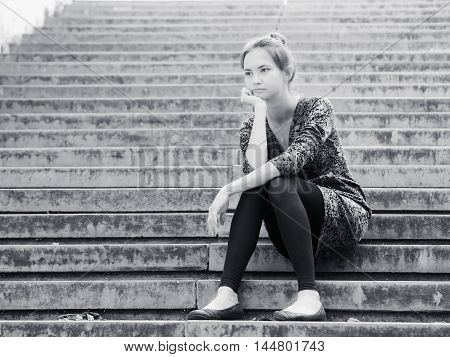 Sad lonely young woman sitting on steps. Portrait of serious girl with facial expression outdoors. Black and white image