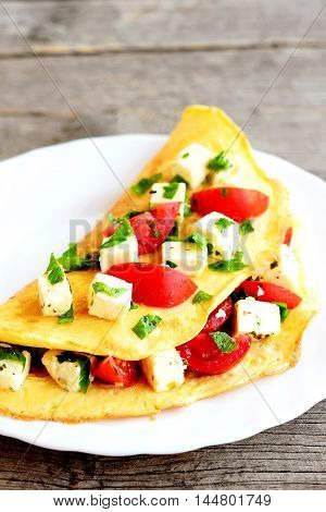 Omelet with cheese, tomatoes and parsley on a plate on old wooden background. Stuffed omelet recipe. Closeup