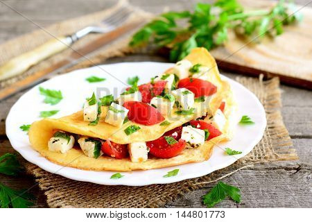 Omelette with cheese, tomatoes and parsley on a plate on old wooden background. Stuffed omelette dish. Vintage style. Closeup