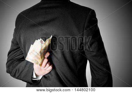 Businessman hinding fifty euro bank notes behind his back