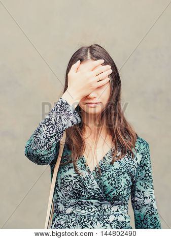 facepalm girl. Portrait of young woman doing facepalm posing against gray wall background. Vertical