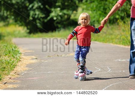 mother helping little daugther to roller skate, kids sport