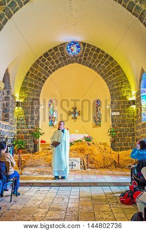 TABGHA ISRAEL - FEBRUARY 22 2016: The worship in Church of the Primacy of St Peter the Mensa Christi (the Table of Christ) located on the background of the Priest on February 22 in Tabgha.