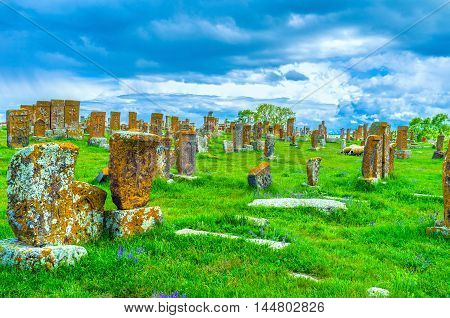 The old carved khachkars on the bright green meadow of Noratus Cemetery in Gegharkunik Province Armenia.