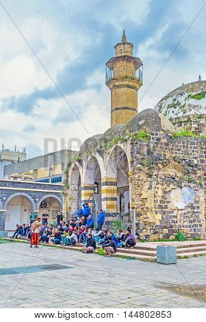 TIBERIAS ISRAEL - FEBRUARY 22 2016: The performance of the street artist at the entrance to the abandoned Great Al-Omari Mosque on February 22 in Tiberias Israel.