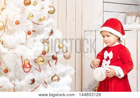 Little girl in red costume decorates new year tree with ball in decorated room