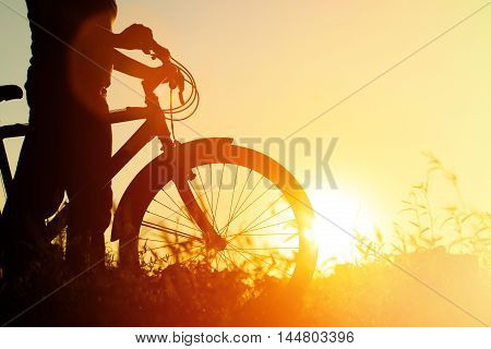 silhouette of young woman riding bike at sunset, sport and active lifestyle
