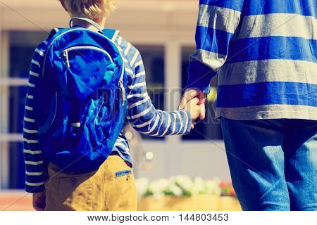 father holding hand of son on going to school or daycare