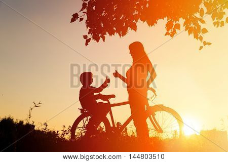 Silhouette of happy mother and little son biking at sunset