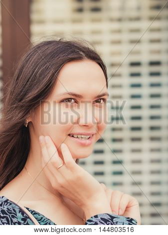 Close up of smiling young woman looking away and holding hand at face. Vertical portraite city outdoors