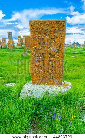 The orange khachkar of tuff covered with lichen and located at the Noratus Cemetery Gegharkunik Province Armenia.