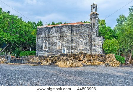 The Church of the Primacy of St Peter located in the lush green garden and one of its sides looks at the Kinneret Lake Tabgha Isael.