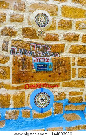 SAFED ISRAEL - FEBRUARY 22 2016: The donation box built in the stone wall and surrounded by circle tiles and hebrew inscriptions on February 22 in Safed.