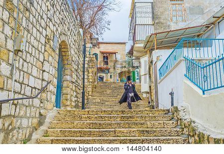 SAFED ISRAEL - FEBRUARY 22 2016: The young Orthodox Hasid goes down the stairs in the old town on February 22 in Safed.