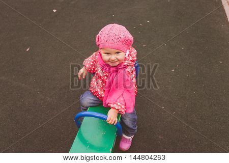 cute little girl playing on playground outdoors, kids outdoor activities