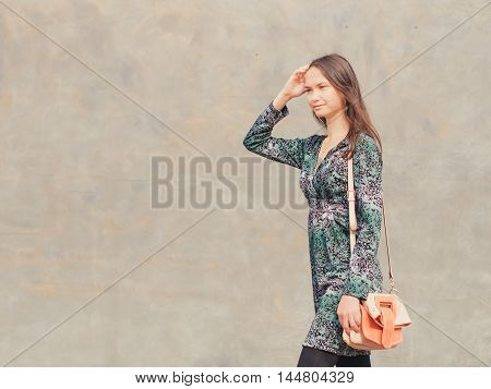 Side view of caucasian woman walking on city street in front of gray wall. Copy space