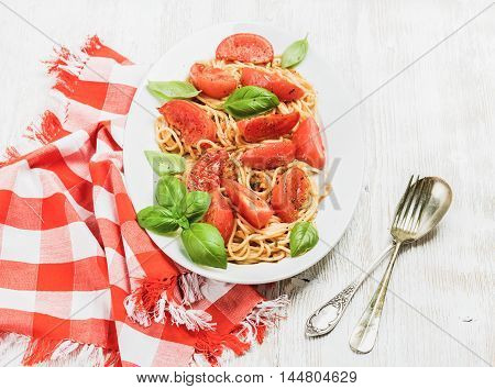 Pasta dinner. Spaghetti with roasted tomatoes and fresh basil in oval dish over white wooden background, selective focus, horizontal composition