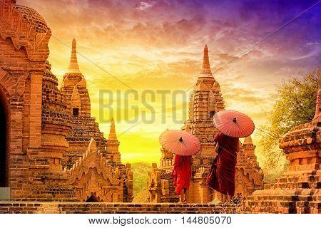 Novice monk with red umbrella walking around bagan Pagoda Bagan Myanmar.