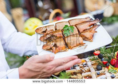 Fish.Barbecue smoked fish on catering. chef serve grilled fish.