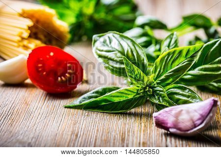 Fresh basil leaves tomatoes garlic an spaghetti on wooden table.
