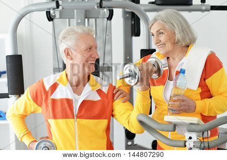 Active smiling senior couple exercising in gym