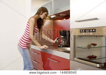Portrait of beautiful young adult attractive pretty woman standing at the kitchen counter - Indoor