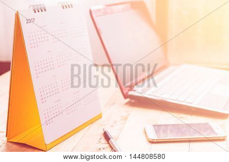 White paper desk spiral calendar 2017 on wood desk with soft focus color filtered background.