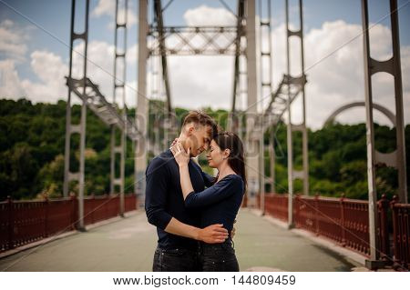 Positive couple in love on the bridge hugging together