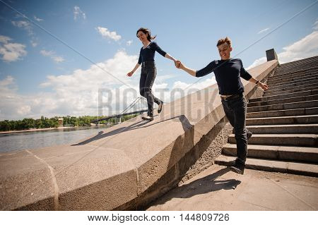 Happy young couple holding hands and running down the stairs in summer