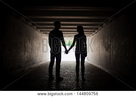 Silhouette of young happy couple holding hands
